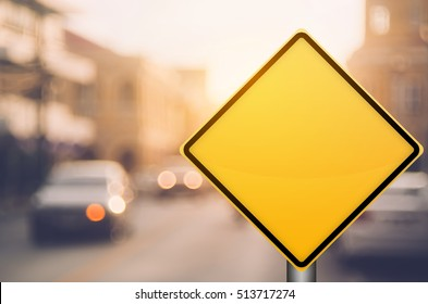 Empty yellow traffic sign on blur traffic road with colorful bokeh light abstract background. Copy space of transportation and travel concept. Retro tone filter color style.