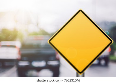 Empty yellow traffic sign on blur traffic road with colorful bokeh light abstract background. Copy space of transportation and travel concept. Retro tone filter effect color style.
