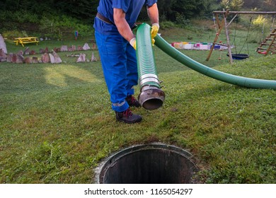 Emptying household septic tank. Cleaning and unblocking clogged drain with vacuum pipe.
