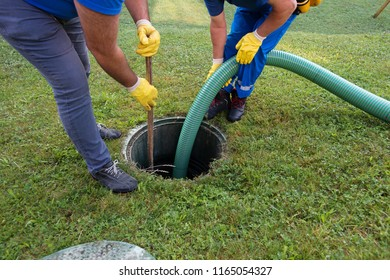 Emptying household septic tank. Cleaning and unblocking clogged drain with vacuum pipe and spear.
