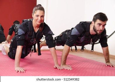 EMS male and female working out together, doing push ups in gym  while connected to muscle stimulator