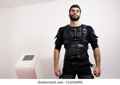 EMS, portrait of handsome man next to electro muscle stimulation machine