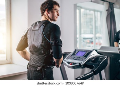 ems training. Fit Man wearing black electromiostimulation suit preparing for running on treadmill near window