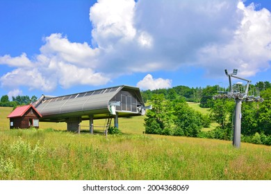 Emtpy chairlift in ski resort. Shot in summer with green grass and no snow.