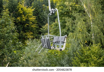 Emtpy chairlift in ski resort station, temporarily closed during summer season. With green trees and no snow.