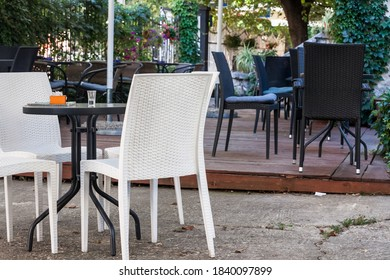 Emtpy chairs and tables in the garden and terrace of a cafe bar restaurant, with nobody to seat and drink, in summer.