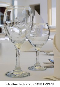 Emtpy transparent wine glasses on a table in a fine restaurant outdoors, close up