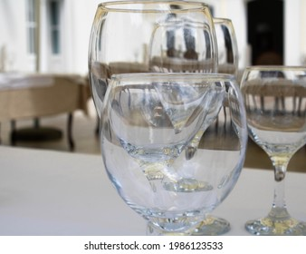 Emtpy transparent wine glasses on a table in a restaurant outdoors, close up