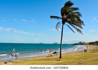 Emu Park, Queensland, Australia - December 27, 2017. Beach in Emu Park, QLD, with people, palm tree and surf rescue flags.