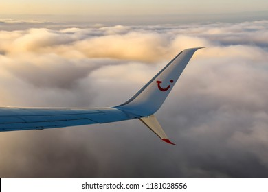 EN ROUTE BIRMINGHAM, ENGLAND TO VERONA, ITALY - SEPTEMBER 2018: Logo of the TUI holiday company on the wing tip of an airliner flying over clouds in early morning light.