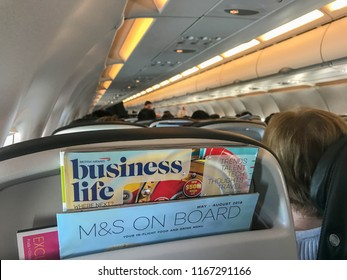 """EN ROUTE PRAGUE TO LONDON HEATHROW - AUGUST 2018: British Airways in-flight magazine in seat pocket with """"M&S On Board"""" menu for food provided by Marks & Spencer."""