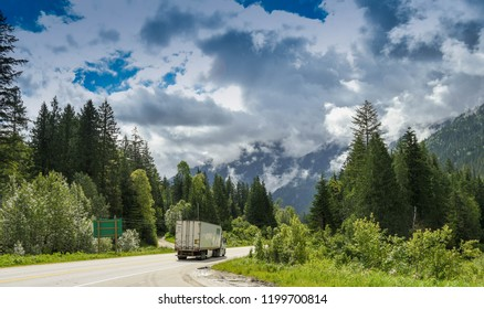 EN ROUTE VANCOUVER TO REVELSTOKE, BRITISH COLUMBIA, CANADA - JUNE 2018: Articulated truck driving down a road in British Columbia with mountains and trees either side.