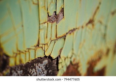 Enamel cracking and flaking off a rusted metal surface