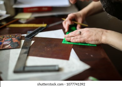 enamel master puts a sketch on a copper plate, concept creativity and creative workshop, soft focus, toning