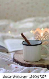 Enamel mug with hot drink and cinnamon stick, lit candle and open book on the bed. Selective focus, bokeh lights.