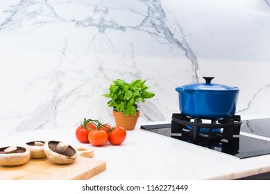 Enamel pot cooking on gas hob with ingredients on marble bench top with marble splash back  in contemporary kitchen in Australian home