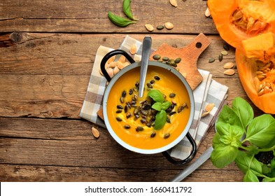 Enamel pot of cream pumpkin, carrot soup with fresh basil, pumpkin seed, knife and laddle on rustic wooden table. Top view.