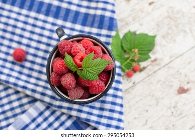 enamel vintage cup full of raspberries, summer taste on a blue striped tea towel