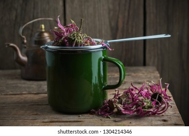 Enameled cup of healthy echinacea tea with tea infuser, dry coneflower herbs and vintage teapot on wooden table.