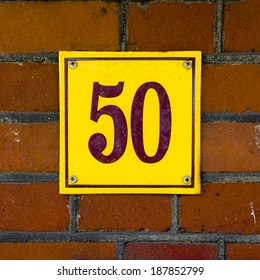Enameled house number fifty. Brown lettering on a yellow background.