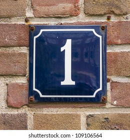 enameled house number one. White lettering on a blue background