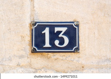 Enameled house number thirteen (13) on a plastered wall