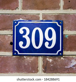 enameled house number three hundred and nine. White lettering on a blue background