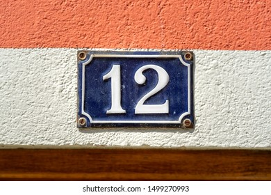 Enameled house number twelve (12) in a horizontal striped composition