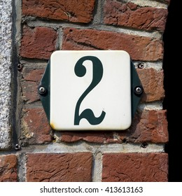enameled house number two, green numeral on a white background.