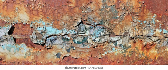 Enamelled  cracked  surface of the door hood of the old truck car was painted in yellow blue and red colors. Vintage texture panoramic concept