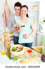 Enamored couple drinking wine in the kitchen at home