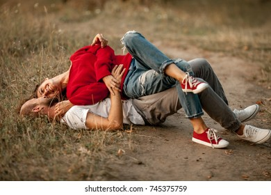 Enamored couple lies, smiles and embraces on forest path. Girl is lying on guy.