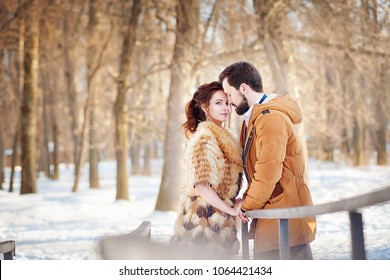 Enamored man with a beard and a woman in a fur coat stand close to each other against a winter forest on a sunny winter day.