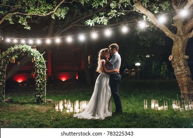 Enamored newlyweds gently embrace. Wedding ceremony in nature. The lights of the electric garland illuminate the wedding party.