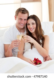 Enamoured couple drinking champagne with strawberries lying in bed at home