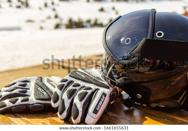 Encamp / Andorra - February  2020:  Ski equipment: helmet and mask,  gloves lie on a wooden table on a background of mountains, lunch time.  The concept of vacation at a ski resort.