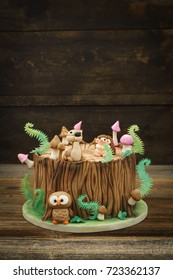 Enchanted forest woodland themed fondant cake with a hedgehog, deer, owl, tree trunk, ferns, mushrooms and leaves on wooden background with copyspace