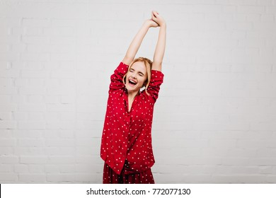 Enchanting blonde woman in red sleepwear stretching on light background with smile. Cute european girl in pajamas enjoying good morning and laughing.