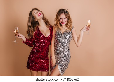 Enchanting curly girls spending time at new year party and enjoying champagne. Indoor portrait of stylish ladies dancing together on light background and laughing.