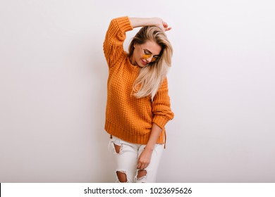 Enchanting female model in trendy ripped pants looking down while posing in studio. Indoor portrait of graceful blonde girl in bright cardigan and yellow sunglasses isolated on white background.