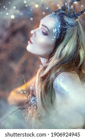 An enchanting forest nymph with blue eyes and blonde hair covered with ice. Fairytale character.
