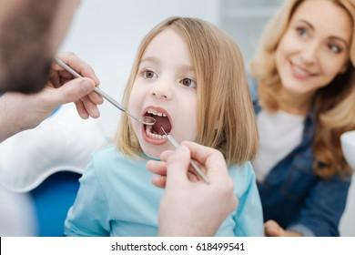 Enchanting girl showing her teeth to doctor