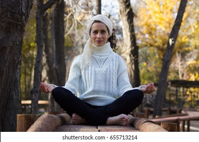 Enchanting mature woman practices yoga in lotus asana sitting on wooden path at the park. Middle aged lady in padmasana pose. Female yogi leisure time, outdoor activity, healthy lifestyle concepts