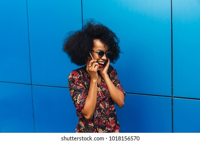 Enchanting smiling young african woman in sunglasses having pleasant conversation by cell phone, looking away. Dressed in bright blouse.