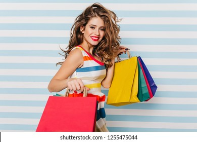 Enchanting young woman laughing after shopping. Pleasant long-haired girl holding paper bags from favorite store.