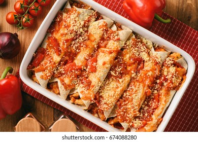 Enchiladas - mexican food, tortilla with chicken, cheese and tomatoes. Cooking process.