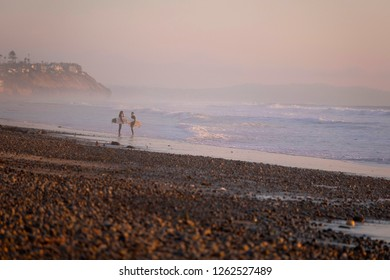 Encinitas, California / USA 12/18/2018     Two surfers walk along the beach at sunset holding their surfboards as they return from surfing in San Diego California a world class surfing destination