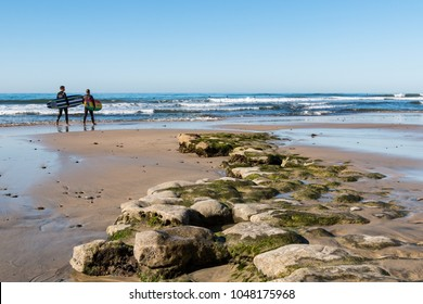 ENCINITAS, CALIFORNIA/USA - FEBRUARY 24, 2018:  Two male surfers walk past an algae-covered reef at low tide on Swami's Beach, a famous surfing mecca in San Diego County.