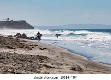 ENCINITAS, CALIFORNIA/USA - OCTOBER 4, 2016:  Two male surfers head out to sea carrying surfboards on Beacon's Beach in Encinitas, California.