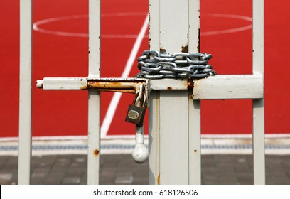 Enclosed basketball court with metal chain and padlock